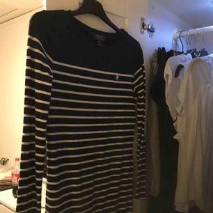 En tjockare vit och marinblå klänning från Ralph lauren i barnstorlek L( 12-14år)  Frakt:50kr