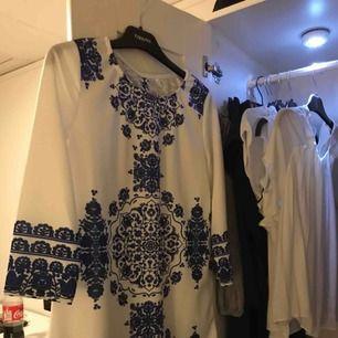 En jättefinklänning i vit men mönster i marinblått! Aldrig använd då den är väldigt liten i storleken, så skulle säga den är XXS/XS  Frakt: 40kr