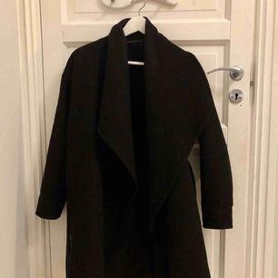Svart kappa från MANGO med bälte i midjan. Strl S och använd en höst. Medeltjock i tyget :-) Möts upp i Stockholm!