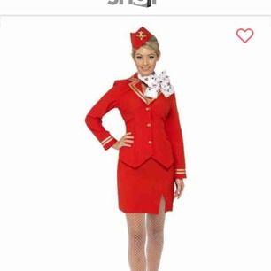 Flygvärdinna outfit strl S  Använd 1 gång, ingår kavaj, kjol, hatt samt scarf.  Kan hämtas i Spånga/Vällingby eller så står köparen för frakt via Postnord.