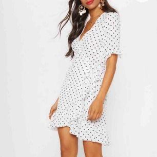 Säljer en jättefin vitprickig omlottklänning! Alla lappar är kvar men säljer för att den är för liten på mig!