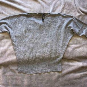 Grå sweater med fungerande dragkedja på baksidan