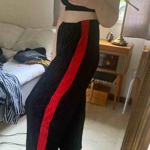 Skitsnygga luftiga svarta byxor med rött revär. Passar mig som brukar ha M och har också ett snöre i midjan. Priset är utan frakt.