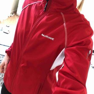 Sportjacka, röd, tunn. Scandinavian sportswear, vindjacka, står emot regn. Använd och lite bortskavt på texten på ryggen, se bild. Passar perfekt med hoodie under när det är lite kallare.