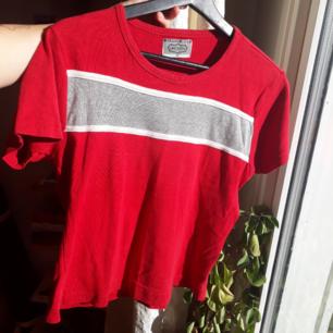Vintage röd t-shirt med en grå horisontell rand på. Randen är något sne men det ger den lite karaktär.😉