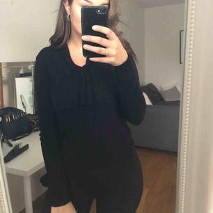 En svart tröja med knytning fram. Köparen står för ev frakt:)