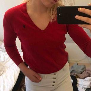 Röd Polo Raulph Lauren v-ringad långärmad tröja. Skitsnygg passform på tröjan och den är väldigt tunn och ett skönt material att bära. Supersnygg!!