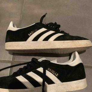 Ett par adidas skor i modellen Gazelle  Svarta mocka med vita och guldiga detaljer  Använda ett par gånger men är i bra skick 😊