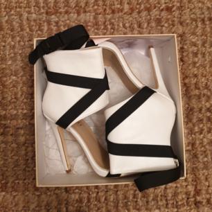 Vita heels med svarta band från Simmi london i stl 37. För små för mig. 😞 Adrig använda.