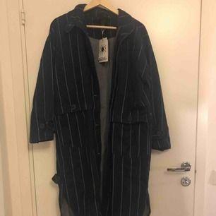 Lång randig kappa från Monki i storlek XS/S. Aldrig använd med prislapp kvar. Möts på Kungsholmen annars betalar den som köper frakten
