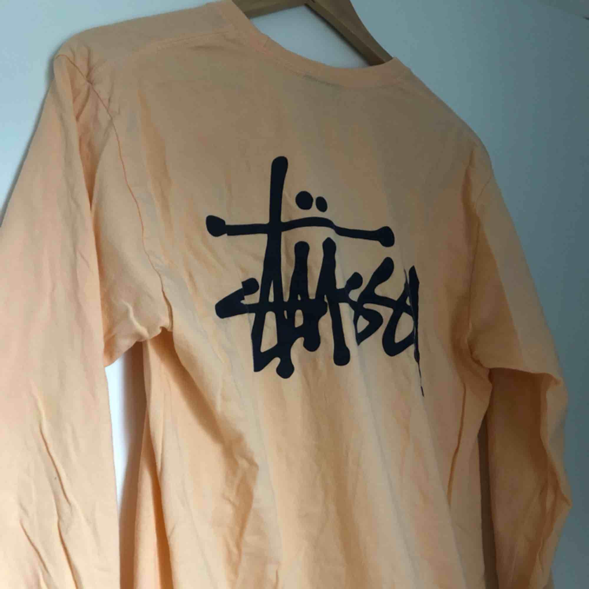 Härlig longsleeve från Stüssy i aprikosfärg! . T-shirts.