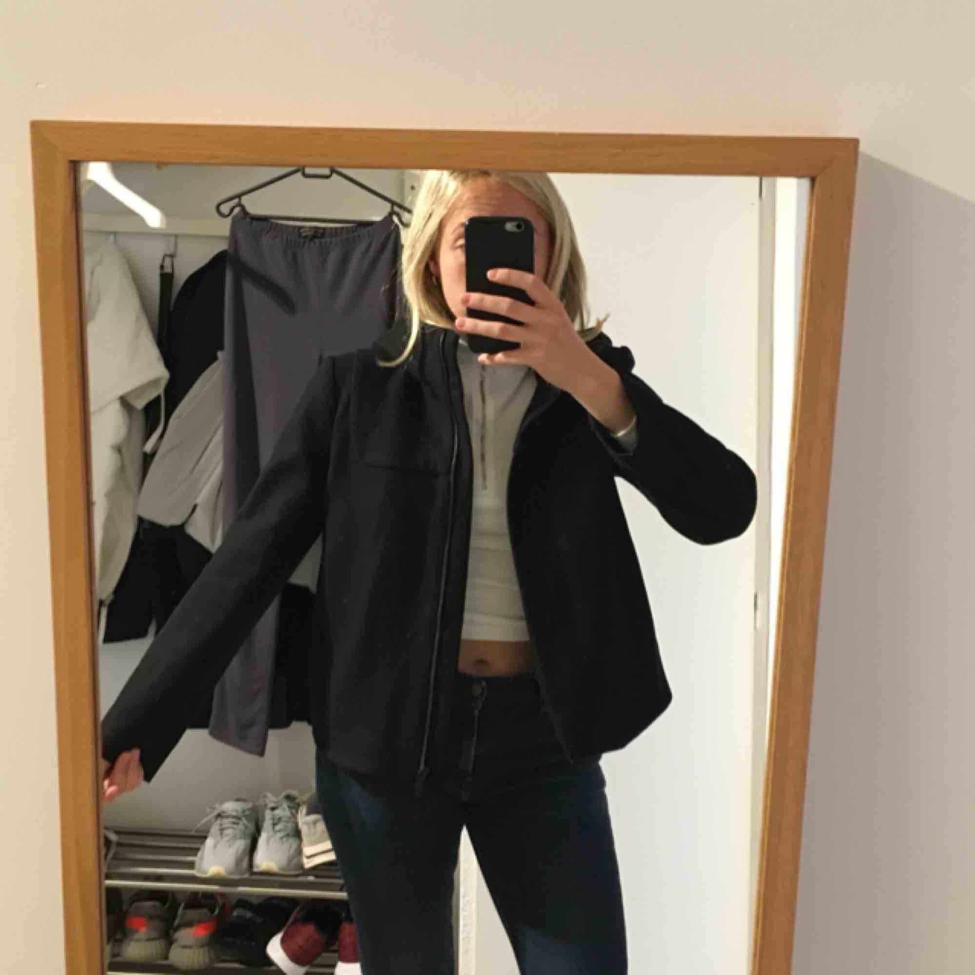 Svart jättefin jacka i 80% ull från COS. Midjekort med stor huva och rymliga fickor. Jackan är tunn men varm även under vintern då den är av ull, dessutom bred i modellen så den rymmer flera tröjor under! . Jackor.