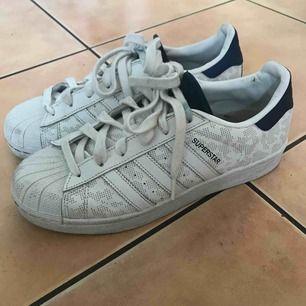 Originella Adidas Superstar som är vita och blåa med ett diskret tryck på. Innersulan är lite smutsig men går enkelt att byta ut. Blåa detaljer där bak som blir som reflexer med flash. Storlek 39 1/3