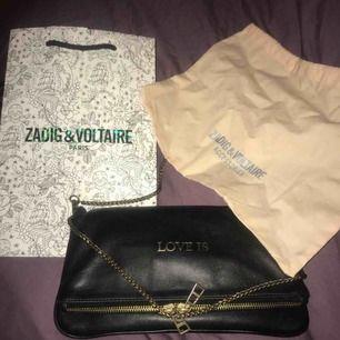 """Zadig väska i bra skick, dustbag och orginalpåse medföljer. """"LOVE IS"""" tryck på ena sidan och ZV loggan och dragkedja på andra. Den går att använda åt båda hållen, så man får två väskor i en;)  Köpt för 3330kr på Zadig & Voltaire butiken i Stockholm"""
