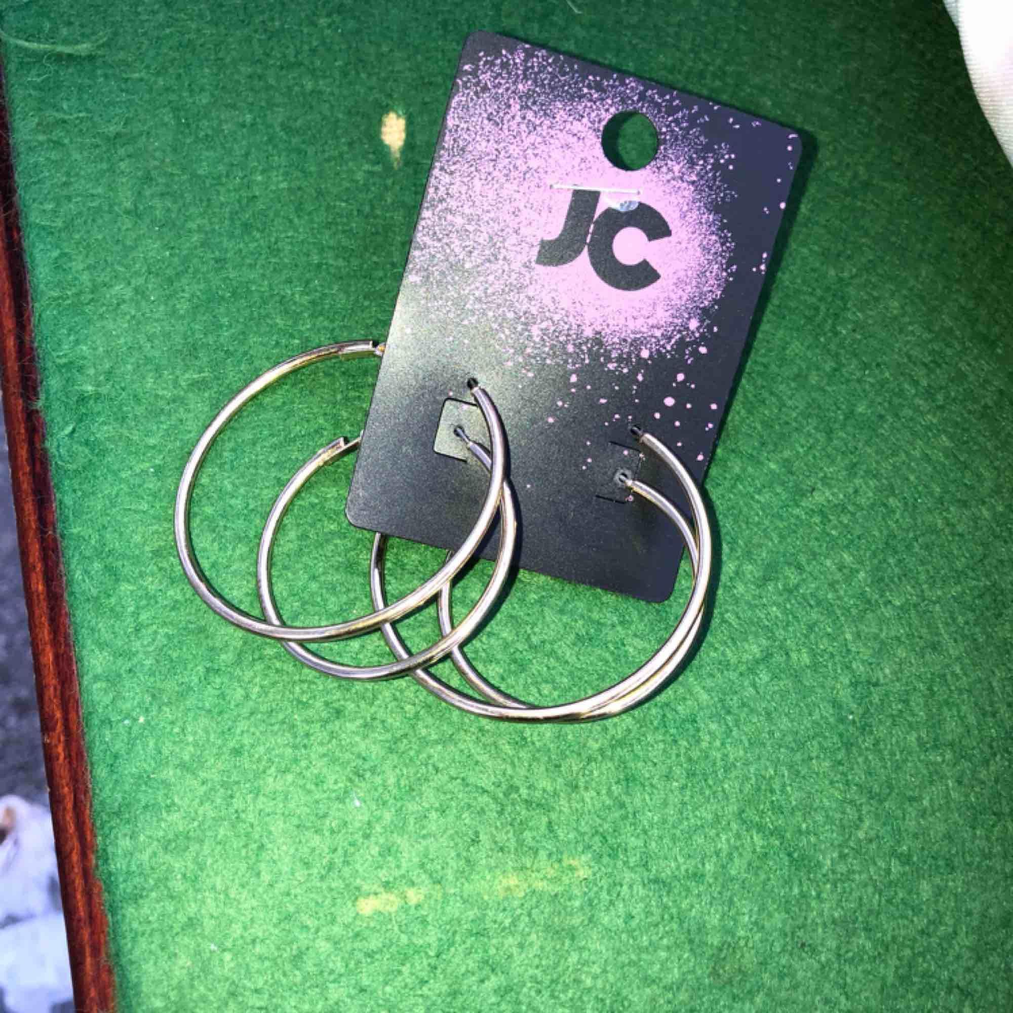 Man ser ej tydligt på bild men det är 2 par guldiga hoops.. Accessoarer.