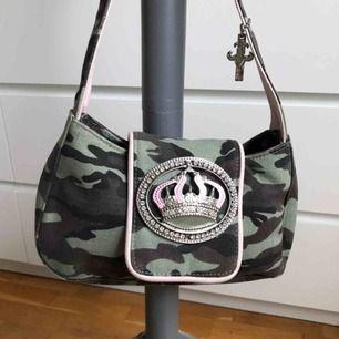 Liten camo/rosa Friis&Company väska. Mått: Längd ca 26cm, höjd ca 14cm. Det fattas en kristallsten längst ner, i övrigt fint skick. Frakt 36kr tillkommer