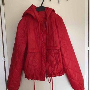 Röd jacka med huva från H&M. Aldrig använd. Säljer pga röd passar inte mig :( sidfickor med tryckknapp. Lång ärm med resår vid armslut. På jackan står storlek S men passar också mig som har M