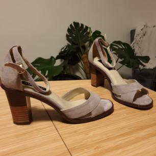 Klackskor i mockamaterial, ljusgrå färg. Sköna och fina skor. Endast använda en gång, i perfekt skick. Nypris är 1000 kr.