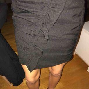 En svart kjol med volanger på framsidan, fint sik använt några gånger
