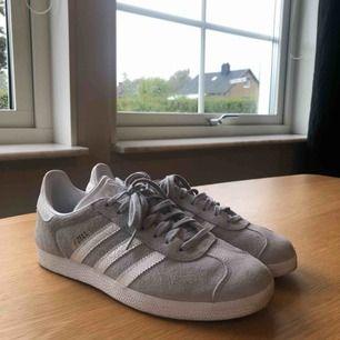 Säljer ett par ny gazelle skor från Adidas i mycket bra skick!  Skorna är i mocka i en ljusgrå färg, med guld detaljer. Skorna är använda ett fåtal gånger. Storlek: 39 1/3