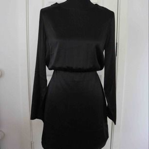 Säljer en svart klänning i ett siden material med öppning i ryggen. Klänningen är i nytt skick! Storlek: 40