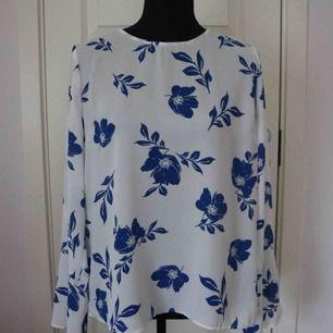 Säljer en vit blus med blå blommar, blusen har knyten vid armarna. I mycket bra skick!