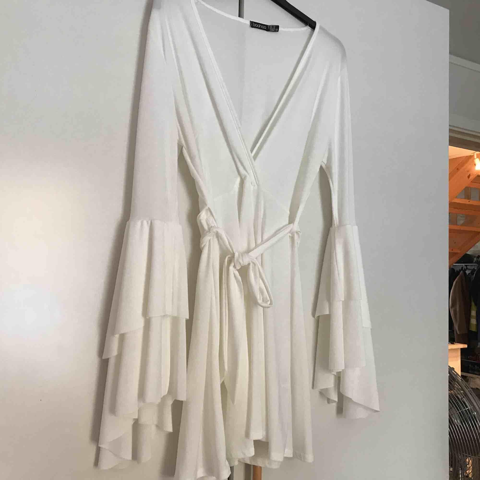Vit klänning med volangdetaljer och skärp runt midjan.   Kan mötas upp i Stockholm. Köparen står annars för frakten. . Klänningar.