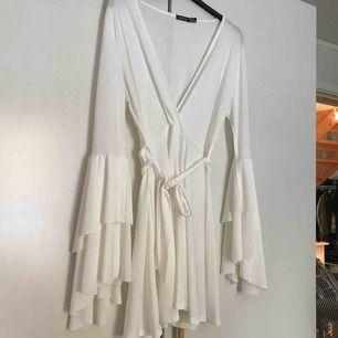 Vit klänning med volangdetaljer och skärp runt midjan.   Kan mötas upp i Stockholm. Köparen står annars för frakten.