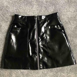 Super snygg lackad kjol från Monki. Använd endast en gång, därmed i väldigt bra skick. Frakt tillkommer och betalning sker via swish.