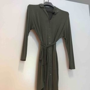 Grön skjortklänning i mjukt material. Ena hållaren för skärpet trasig (se andra bilden).   Kan mötas upp i Stockholm. Köparen står annars för frakten.