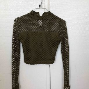 Mesh material, tight, with a slight turtleneck vibe, the arms are well fitted, crop top.