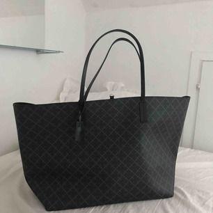 Säljer väska från By Malene Birger i nyskick. Modellen heter Abi tote bag. Storlek: ca 56×33×16 cm. Färg: Charcoal, svårt grå. Väskan passar som shopping bag, det finns mycket plats. Kommer från rök- och djurfritt hem.