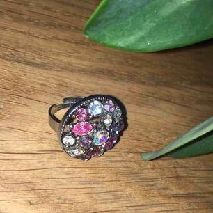 Ställbar ring med fina diamantstenar i olika färger. Frakt ingår i priset.