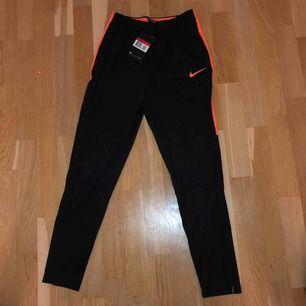 Säljer ett par helt oanvända Svarta Nike långbyxor med en orange stripe på sidan. Storlek L barn, 147-158 cm, 12-13 år.  Säljer på grund av att jag köpt fel storlek och då jag skulle byta var de slut i storlek.