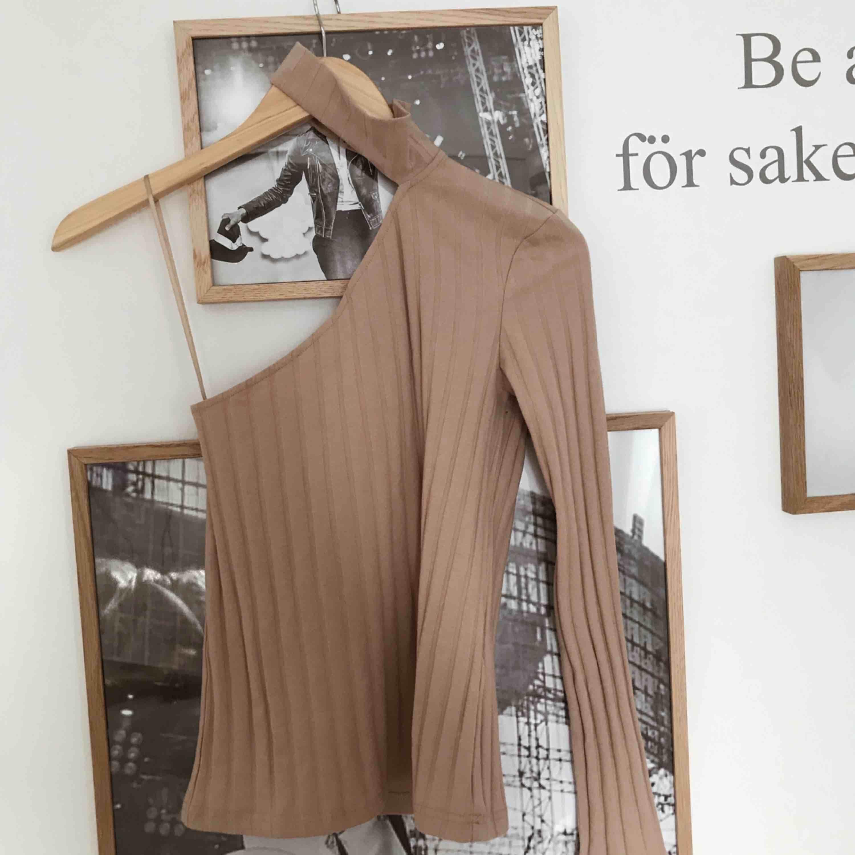 En beige tröja med en ärm samt chocker. Oanvänd, köparen står för frakt! . Toppar.