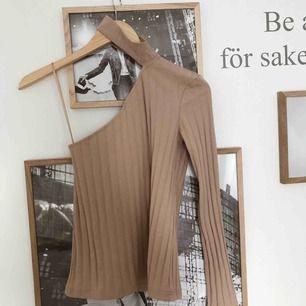 En beige tröja med en ärm samt chocker. Oanvänd, köparen står för frakt!