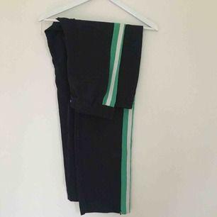 Coola och streetiga mörkblå byxor från Monki med grön+vitt sträck på sidan. Säljer pga alldeles förstora för mig. Bekväma och bra skick.  Kan mötas upp i Lund eller Kristianstad, annars står köparen för frakt.