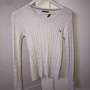 En supersnygg vit kabelstickad tröja från Gant. Den är i nyskick förutom lappen som tyvärr har gått av på ena sidan. Passar både XS och S och sitter så bra längs kroppen!
