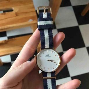 Mellanstor, äkta Daniel Wellington- klocka som jag inte använder längre. Funkar perfekt men vet dock inte om den ör i rosé-guld eller bara guld då det skiftar lite. Bandet har färgat av sig på det vita men  annars inga skråmor. nypris: 1299kr