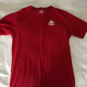 En röd Kappa t-shirt med print där fram och där bak.