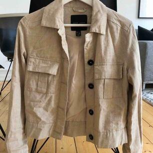 Beige, tunn jacka i linne liknande material från märket New Look. Endast använd vid ett tillfälle, dock har översta knappen på jackan ramlat av (se bild). Skickar med knappen så den går att sy fast igen för den som orkar!