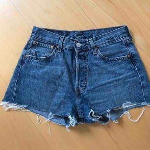Äkta Levis 501 avklippta jeansshorts. Köptes på jeansbolaget för något års sedan och är i bra skick! Storleken på shortsen är W28 men passar perfekt för en person som bär small.