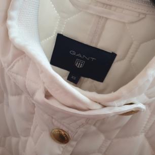 Helt ny GANT jacka.  Inköpt på best of brands våren 2018 för 1 500 sek.   Vit med guldiga detaljer och vadderad.   Kan nötas upp i Huddinge, Älvsjö, Årsta, Globen & Västberga