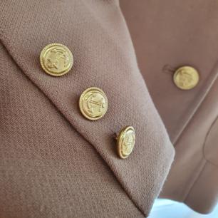 Kanske den mest klassiska och snyggaste höstkappan du kan tänka dig. Den perfekta beiga färgen tillsammans med guldiga detaljer och rött innertyg. Lyx i dess billigaste form.  Inköpt på H&M  Sparsamtanvänd   Kan nötas upp i Huddinge, Älvsjö, Årsta, Globen & Västberga