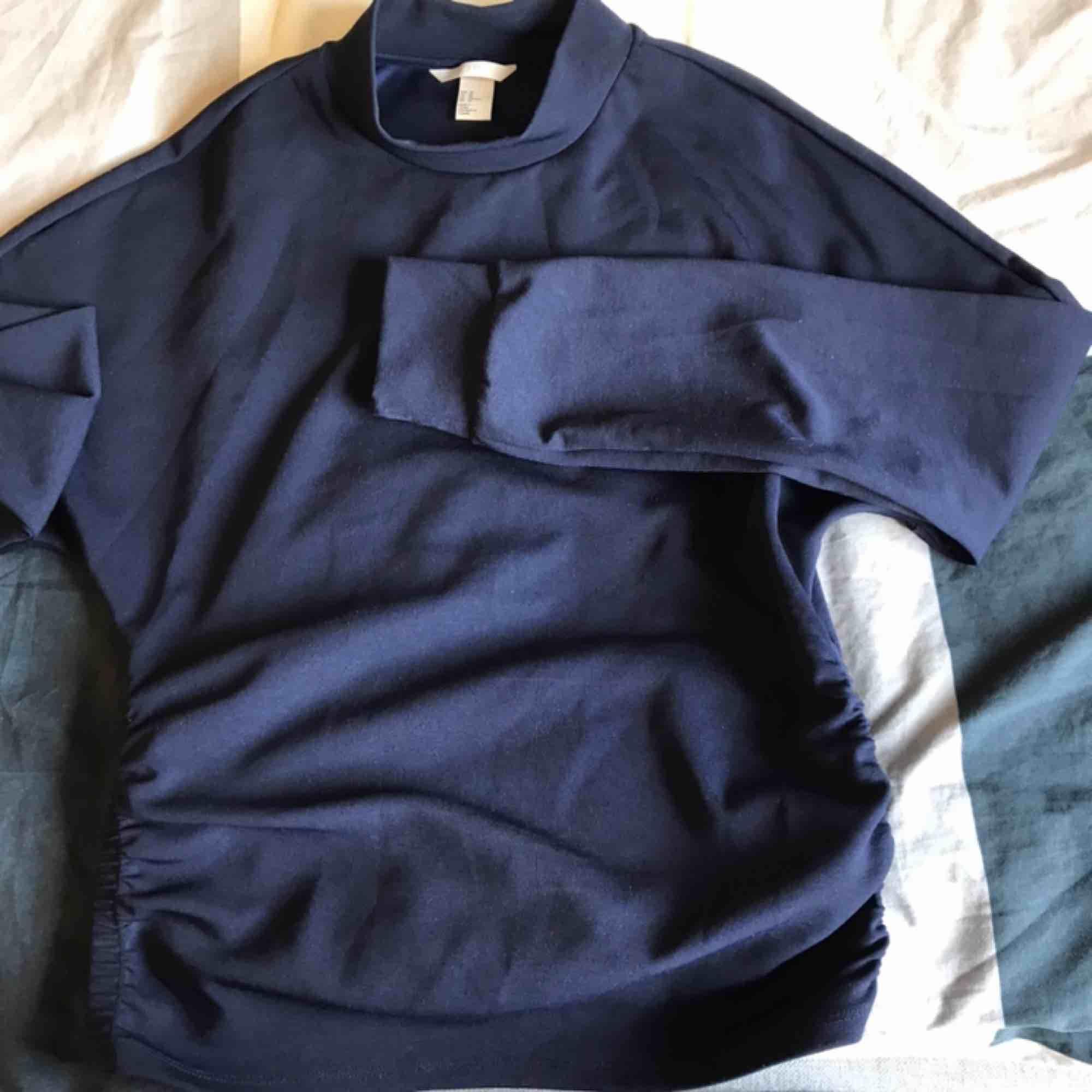 Mörkblå långärmad tröja från h&m med resår på sidan så den sitter åt lite runt magen så man får fin figur. Använd enstaka tillfällen. Köparen står för frakten😃. Toppar.