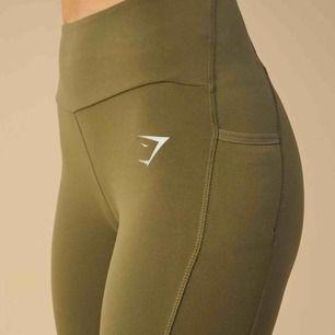 Gymshark Aspire Leggings i färgen Khaki. Använd ett par gånger men är fortfarande i gott skick. Inköps pris 699kr.   Har fickor på sidorna och är mid highwaisted.