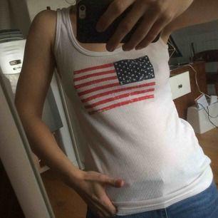 Vitt linne med USA flagga på. Står medium men passar mig som är xs/s. Köparen står för frakten