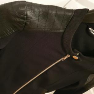 Svart kofta/jacka med fejk läder detaljer.  Stretching och riktigt bekväm.