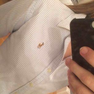 Ralph Lauren skjorta i slim fit, 100% bomull. Blåvitrandig med ikoniska loggon broderad på bröstet. Snygg, skön o tidlös! Säljer en nästan likadan till i rosa Köparen står för frakt
