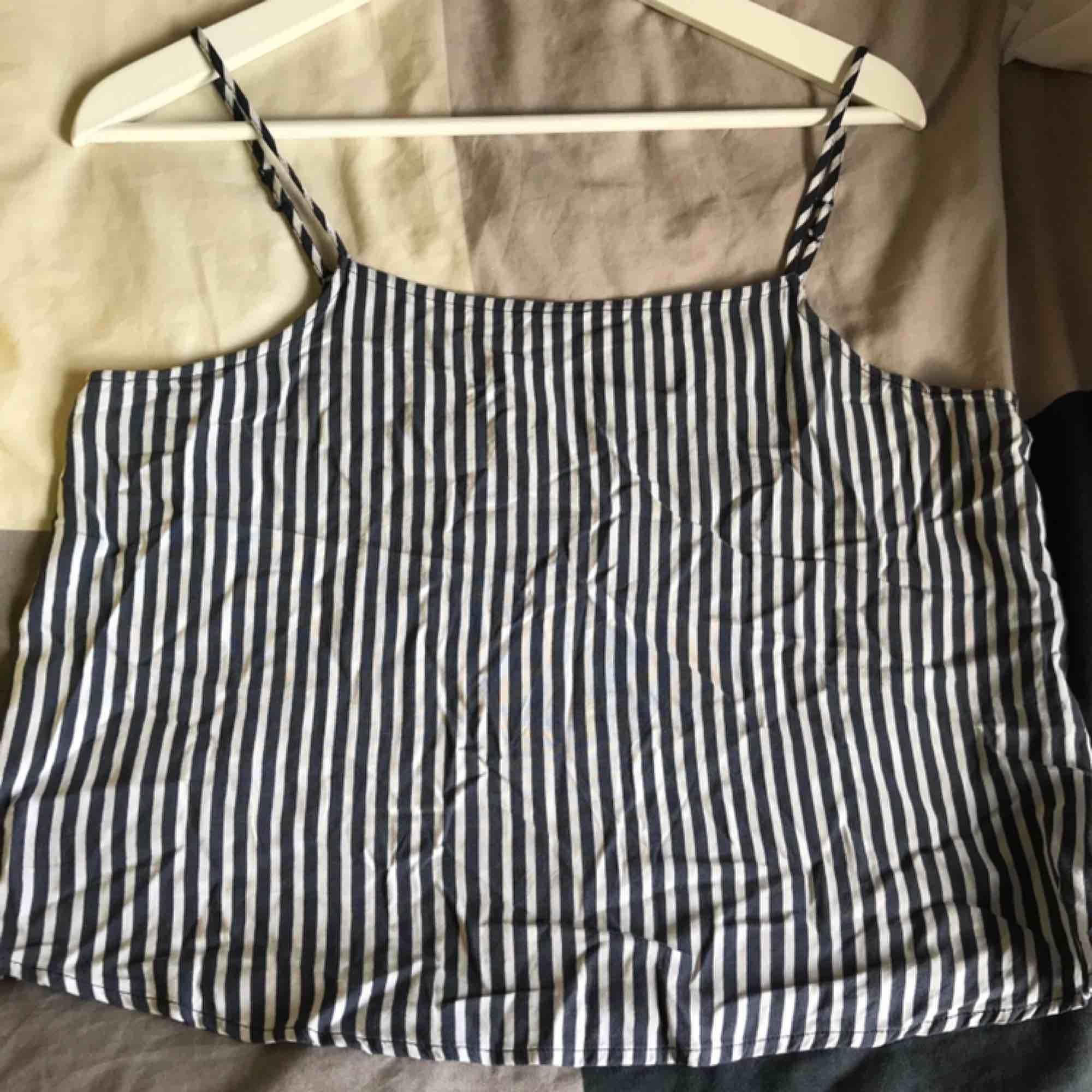Gulligt linne från H&M som inte är speciellt använt. Den är marinblå/vit randigt och kortare i modellen. Den har även justerbar snöre. Köparen står för frakten 💙💙. Toppar.